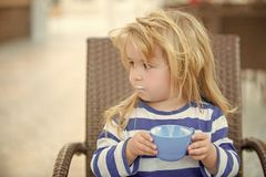 Nutrition and growth concept. Health and healthy dieting. Child and childhood. Toddler with long blond hair holding blue cup. Boy drinking milk on chair stock photo