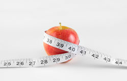 Nutrition and healthy diet concept. With apple and measuring tape Stock Photos