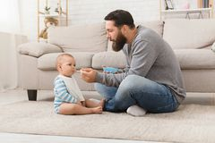 Little boy refuses to eat making unpleasant grimace, isolated over white. Nutrition and healthy eating habits for kids. Little boy refuses to eat daddy`s food stock photos