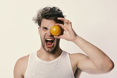 Nutrition and healthy lifestyle concept. Man with orange covering eye. In his hand. Guy with screaming face isolated on light grey background. Athlete with royalty free stock photography