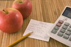 Nutrition information, an apple and a calculator. Apples are on the table, a calculator and a paper with a table caloric Stock Photo
