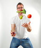 Nutrition Juggle. Image of a man juggling fruits and vegetables Stock Images