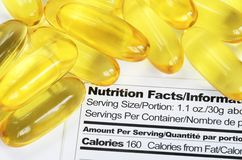 Nutrition label with fish oil pills Stock Photos
