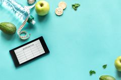 Nutrition Meal Plan. Mockup on tablet with water, fruits and measuring tape. Fitness nutrition, diet, healthy lifestyle concept on blue, top view, copy space royalty free stock photo