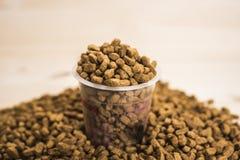 Nutrition sèche d'animal familier avec un haut étroit de tasse de mesure Photographie stock libre de droits