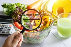 Nutritional information concept. hand use the magnifying glass to zoom in to see the details of the nutrition facts from food