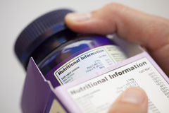 Nutritional information about vitamin pills. Human hand take out bottle with vitamin pills from the box for reading Nutritional information royalty free stock images