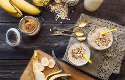 Nutritional smoothie with banana, oat flakes and peanut butter. Fresh homemade nutritional smoothie with banana, oat flakes and peanut butter on rustic wooden royalty free stock photo