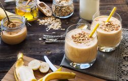 Nutritional smoothie with banana, oat flakes and peanut butter. Fresh homemade nutritional smoothie with banana, oat flakes and peanut butter on rustic wooden Stock Images