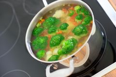 Nutritional soup with green broccoli in pan on hob. Nutritional soup with green broccoli in metal pan on hob Stock Photography