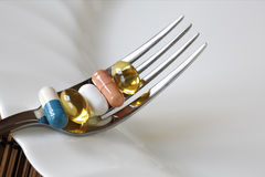 Nutritional supplement. Medicine and nutritional supplement on a fork stock photos