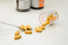 Nutritional supplement (pills) in spoon and containers Stock Photo