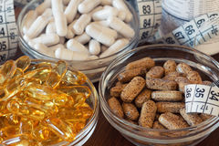 Nutritional supplements in capsules and tablets, on wooden background Royalty Free Stock Images