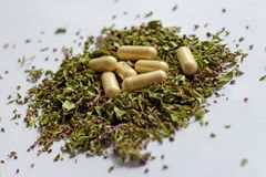 Nutritional supplements pills and capsules on dried herbs background. Alternative herbal medicine, naturopathy and homeopathy royalty free stock photography