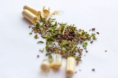Nutritional supplements pills and capsules on dried herbs background. Alternative herbal medicine, naturopathy and homeopathy royalty free stock photos