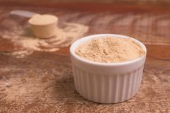 Nutritional yeast in a bowl. Over a wooden table stock photo