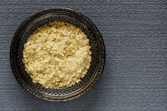 Nutritional Yeast Flakes. Top view of dried nutritional yeast flakes on a vintage metal plate on a gray, textured background royalty free stock photos