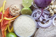 Nutritional Yeast and Veggies. Nutritional yeast surrounded by other fresh ingredients for creamy vegan peppers and onions royalty free stock image