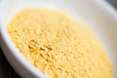 Nutritional Yeast. In a white bowl ready to add to a recipe. High in B vitamins and protein royalty free stock photography