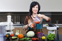 Nutritionist blended smoothie. Smiling nutritionist has just blended smoothie and is pouring it into glass Royalty Free Stock Photography