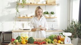 nutritionist-blogger talks about healthy eating while standing at a table with lots of vegan food ingredients at home