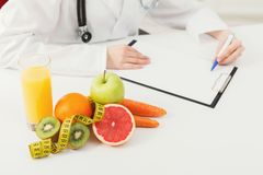 Nutritionist desk with fruit and measuring tape. Nutritionist desk with healthy fruits, juice and measuring tape. Dietitian working on diet plan. Weight loss and Stock Image