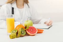 Nutritionist desk with fruit and measuring tape stock image