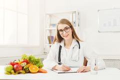 Nutritionist desk with fruit and measuring tape royalty free stock images