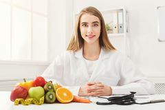 Nutritionist desk with fruit and measuring tape royalty free stock photo