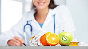 Nutritionist Doctor. Nutritionist female Doctor in her office. Focus on fruit Stock Photography