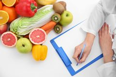 Nutritionist doctor writing diet plan. On table Stock Photo