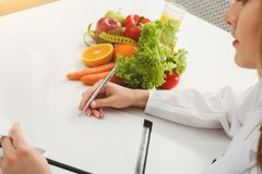 Nutritionist doctor writing diet plan on table. Unrecognizable dietitian making healthy eating menu, copy space for text. Right nutrition and slimming concept Royalty Free Stock Images