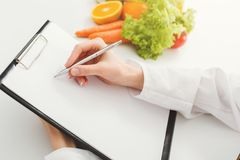 Nutritionist doctor writing diet plan on table. Unrecognizable dietitian making healthy eating menu, copy space for text. Right nutrition and slimming concept Royalty Free Stock Image