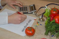 Nutritionist doctor writing diet plan on table. Unrecognizable dietitian making healthy eating menu stock photos