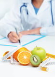 Nutritionist Doctor. Is writing a prescription. Focus on fruit Royalty Free Stock Photo