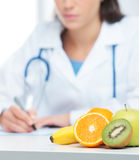 Nutritionist Doctor. Is writing a prescription. Focus on fruit Stock Photo