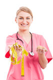 Nutritionist female holding measuring tape and cookies. Like choosing concept isolated on white background Stock Photography