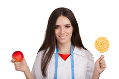 Nutritionist Holding an Apple and a Big Candy Royalty Free Stock Photos