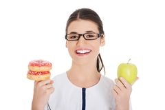 Nutritionist holding a cake and apple. Happy nutritionist holding a cake and apple Royalty Free Stock Photography