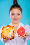 Nutritionist holding a cake and fruit Stock Images