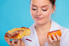 Nutritionist holding a cake and fruit Royalty Free Stock Photography