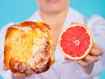 Nutritionist holding a cake and fruit Stock Photos