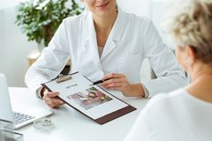Nutritionist holding personalized diet plan. Close-up of nutritionist holding a personalized diet plan for a patient during appointment in the clinic Stock Images