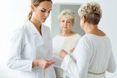 Nutritionist measuring patient`s body circumference. Unsatisfied women looking in the mirror Stock Images