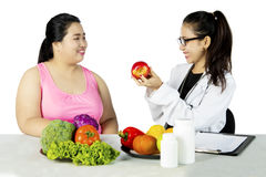 Nutritionist suggesting her patient to eat healthy food. Young nutritionist is suggesting an overweight patient to eat healthy food, concept diet royalty free stock image