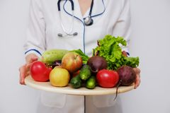 Doctor holding a plate with fruits and vegetables. Nutritionist woman holding a plate with fruits and vegetables stock image