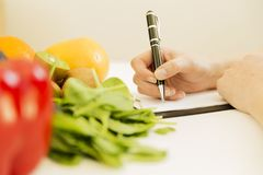 Nutritionist woman writing diet plan on table full of fruits and. Vegetables Stock Photos