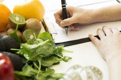 Nutritionist woman writing diet plan on table full of fruits and. Vegetables Stock Image