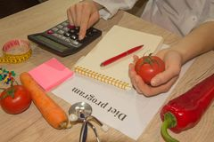 Nutritionist writing medical records and prescriptions with fresh fruits. Concept diet and weight loss Stock Images