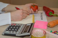 Nutritionist writing medical records and prescriptions with fresh fruits. Concept diet and weight loss Royalty Free Stock Photo